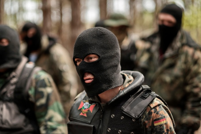 """A volunteer from the """"Vasil Levski"""" Bulgarian Military Veterans Union is seen assembling with other members during a drill in the forest near Nestinarka camp-site. Four to five times a month, they train like an army to face what they consider an invasion to """"Islamize"""" Europe. Tsarevo, Bulgaria 2017. © Matteo Bastianelli"""