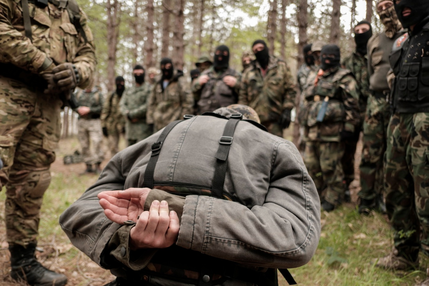 """A volunteer from the """"Vasil Levski"""" Bulgarian Military Veterans Union is seen kneeling during a drill in which the simulation of the capture of a man was carried out in the forest near Nestinarka camp-site. Tsarevo, Bulgaria 2017. © Matteo Bastianelli"""