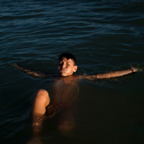 A boy practices floating on his back in the sea in front of the hotel where he has been staying, along with the other evacuees arrived on the Adriatic coast about a year ago, following the earthquake of 24 August 2016 in which almost 300 people died. Grottammare, Italy 2017. © Matteo Bastianelli