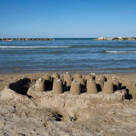 Sand castles by the sea built by a family hosted in one of the hotels on the Adriatic coast, where thousands of earthquake victims have been temporarily staying for about a year now. Grottammare, Italy 2017. © Matteo Bastianelli