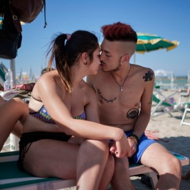 23-year-old Gennaro and 19-year-old Marzia kiss each other on a beach lounger. Marzia and Gennaro met in one of the hotels on the coast where they were staying with the other victims of the earthquake of 24 August 2016. Now they live together in a hotel room. Grottammare, Italy 2017. © Matteo Bastianelli