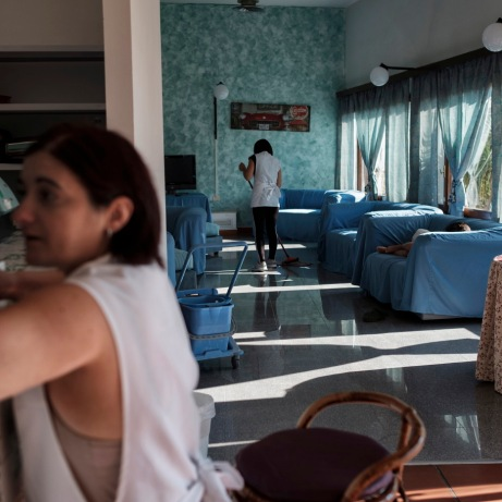 Two women are seen cleaning the lounge of the Marconi hotel while a child sleeps on one of the sofas. Grottammare, Italy 2017. © Matteo Bastianelli